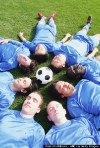 Soccer players lying down around a ball